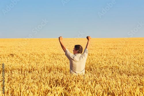 Obraz Farmer walking through a golden wheat field - fototapety do salonu