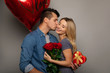 Enjoying the moment. Close up photo of a happy woman with long blonde hair, who had just received a bouquet of roses and two other presents from her boyfriend, who is kissing her in a cheek.