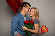 With my eyes closed. Close up photo of a happy couple, who are smiling with their eyes closed and holding a bouquet of roses, a red balloon, and a red present box, celebrating their anniversary.