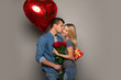 Happy Kisses. A happy woman with long blonde hair had just received a bouquet of roses and two other presents from her boyfriend, who is kissing her in a cheek.