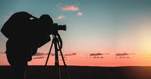 Photographer With A Tripod And Camera Takes A Landscape During Sunset In A Large Open Area