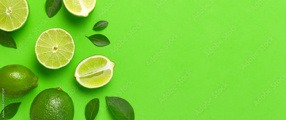 Fototapeta Fresh juicy lime and green leaves on bright green background. Top view flat lay copy space. Creative food background, tropical fruit, vitamin C, citrus. Composition with whole and slices of lime