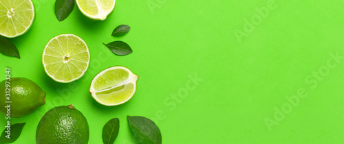 Fotografering Fresh juicy lime and green leaves on bright green background