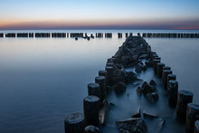 Wooden Breakwater At Sunset On...