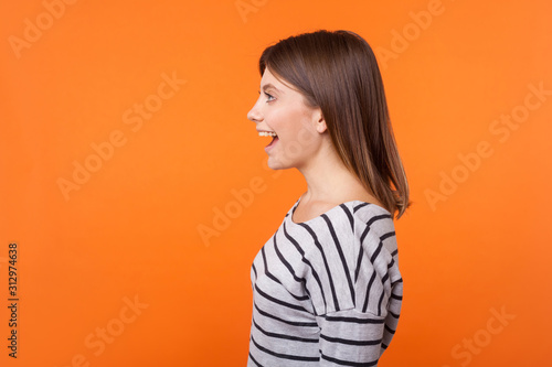 Side view portrait of beautiful amazed woman with brown hair in long sleeve striped shirt standing surprised with open mouth, looking to the left Tablou Canvas