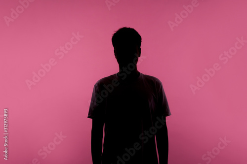 Obraz No name, anonymous person hiding face in shadow, human identity. Silhouette portrait of young man in casual T-shirt standing calm with hands down, indoor studio shot, isolated on pink background - fototapety do salonu