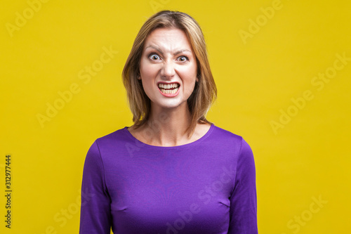 Portrait of beautiful emotional woman in tight purple dress standing with clenched teeth and angry grimace on face, pretending to be aggressive Canvas Print