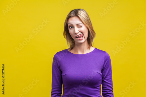 Fotografía Portrait of joyous playful woman in tight purple dress winking and sticking out her tongue, showing funny humorous face grimace, having fun at camera
