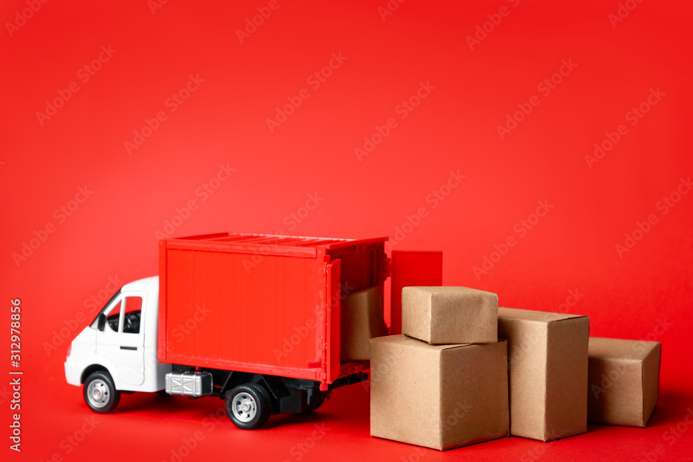 Fototapeta Toy truck with boxes on red background Logistics and wholesale concept