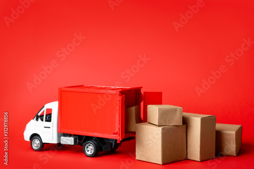 obraz PCV Toy truck with boxes on red background Logistics and wholesale concept
