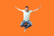 canvas print picture - Full length of crazy overjoyed brunette man in white outfit jumping in air with raised hands, screaming loud for joy, feeling energetic and lively. indoor studio shot isolated on orange background