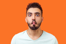 Portrait Of Funny Silly Brunette Man With Beard In Casual White T-shirt Looking At Camera And Making Fish Face With Lips And Big Eyes, Fooling Around. Indoor Studio Shot Isolated On Orange Background
