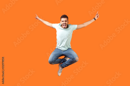 Photo Full length of crazy overjoyed brunette man in white outfit jumping in air with raised hands, screaming loud for joy, feeling energetic and lively