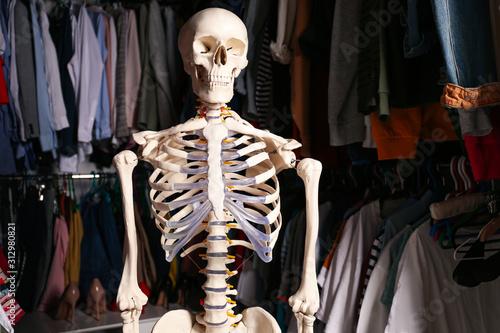 Cuadros en Lienzo  Artificial human skeleton model among clothes in wardrobe