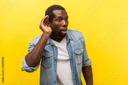 Portrait of attentive surprised man in denim casual shirt with rolled up sleeves putting hand to ear to hear better, listening carefully to rumors Wallpaper Mural
