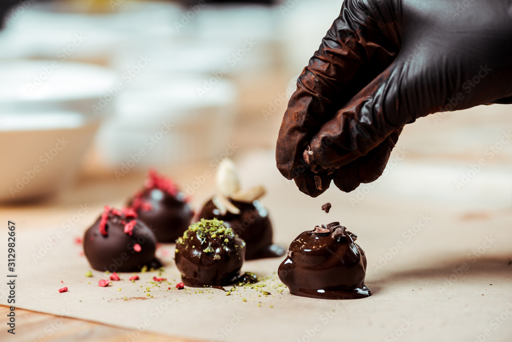 Fototapeta cropped view of chocolatier in black latex glove adding chocolate shavings on fresh made candies