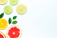 Flat Lay Composition With Slices Of Fresh Lemon Orange Grapefruit Lime Green Leaves On White Background Top View Copy Space. Citrus Juice Concept, Vitamin C, Fruits. Creative Summer Background