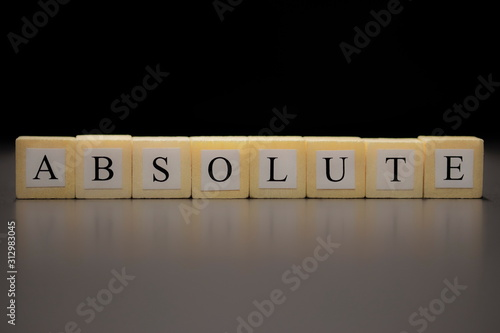 Photo The word ABSOLUTE written on wooden cubes isolated on a black background