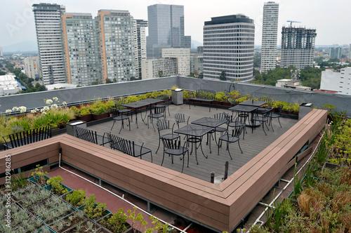 Fototapeta azotea verde con mesas y sillas en la ciudad obraz