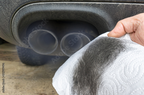 Hand holding a dirty white cloth in front of the smoking exhaust of a car with diesel engine. #312989496