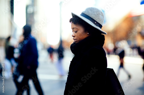 Portrait of a serious young woman in faux fur coat and leather bag crossing a busy urban street looking down