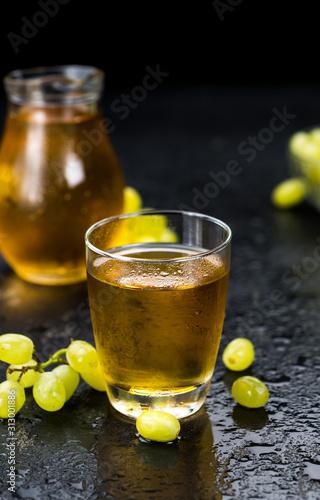 Portion of fresh made Grape Juice on a slate slab (selective focus)