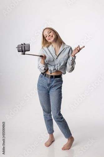 happy young girl making self portrait with smartphone attached to selfie stick Wallpaper Mural