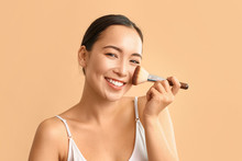 Portrait Of Young Asian Woman With Makeup Brush On Color Background