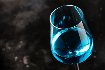 Exotic blue wine, trendy non-classical drink in wine glass on gray background