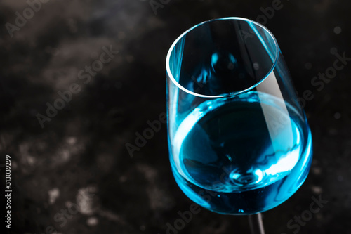 Obraz Exotic blue wine, trendy non-classical drink in wine glass on gray background - fototapety do salonu