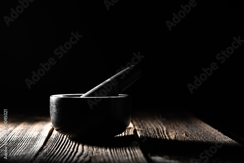 Stone mortar with pestle on black background Canvas Print