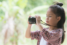 Girl Who Takes Pictures With A Photo Camera In Park On Green Natural Background. Beautiful Smiling Child Holding A Instant Camera.