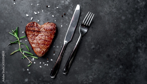 Fototapeta grilled beef steak in the form of a heart with spices, a knife and a fork for Valentine's Day on a stone background with copy space for your text obraz