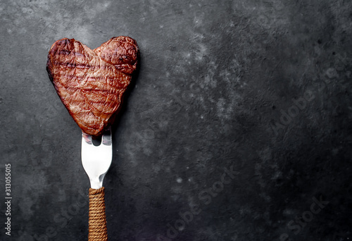 grilled beef steak in the form of a heart on a fork for Valentine's day on a stone background with copy space for your text - 313055015