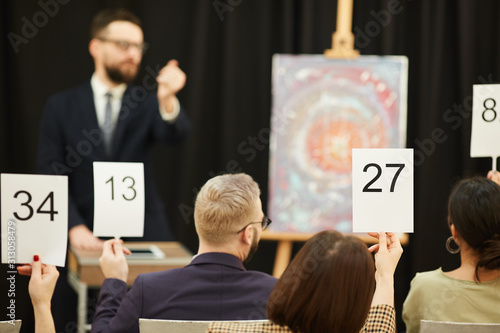 Rear view of group of business people with signs buying a painting during the au Canvas Print