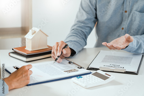 Cuadros en Lienzo  broker agent and customer holding pen, the policyholder and explain discussing for concerning mortgage loan offer for and house insurance