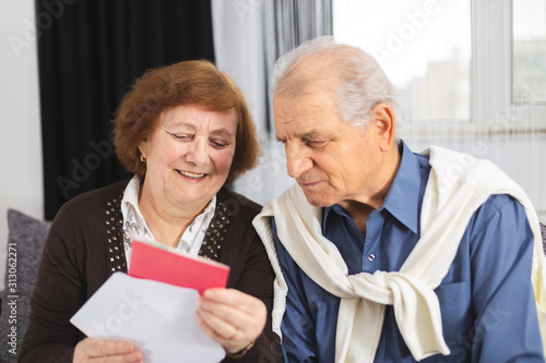 Senior couple standing on the couch and reading a letter received Tapéta, Fotótapéta