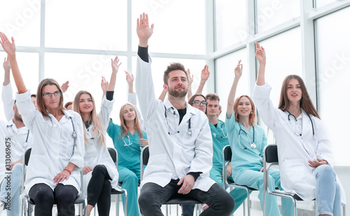 Fotografía medical students raising their hands during the seminar.