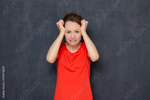 Fotografie, Tablou  Portrait of disappointed young woman raising clenched fists to head