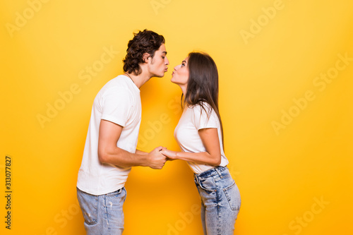 Fotografia Young couple in love kiss isolated yellow background