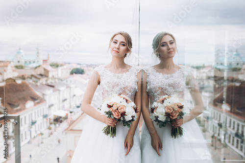 Wedding fashion blondie caucasian girl in beautiful dress outdoors in old city background Canvas Print