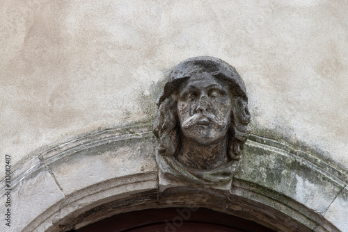 Human face figure as the keystone of an entrance arch to a house Canvas Print