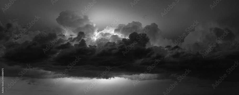 Fototapeta Black and white panorama of lightning flashing between the clouds of a Great Plains thunderstorm