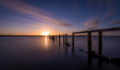canvas print picture - Broken jetty leading into the sea at sunset