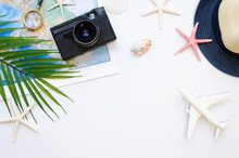 Table Top View Travel Bloggers Accessories, Summer Vacation Items On A White Background. Airplane, Map, A Camera Frame With Copy Space