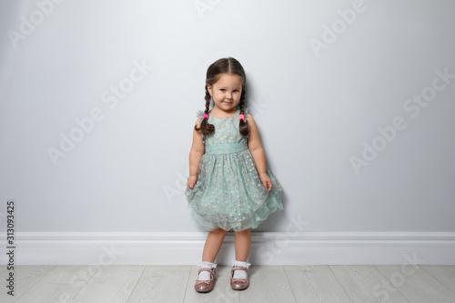 Fototapeta Cute little girl near light grey wall obraz