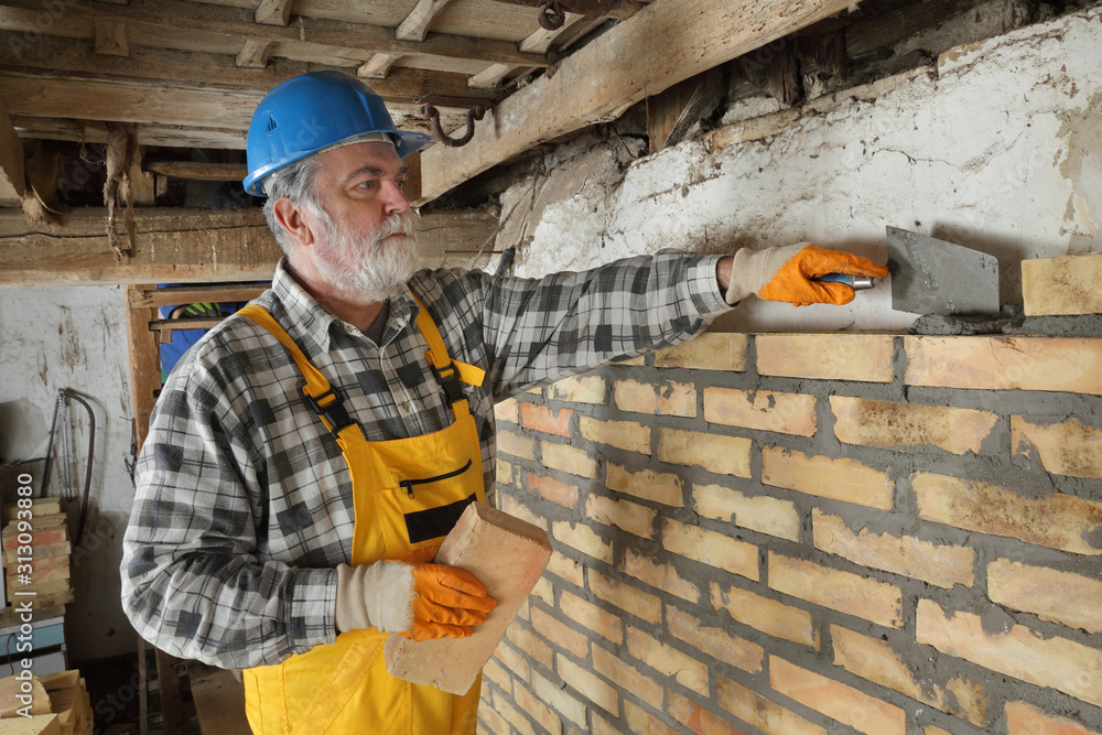 Fototapeta Worker building brick wall in old barn