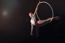 Young Woman Performing Acrobatic Element On Aerial Ring Against Dark Background