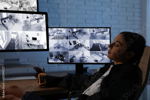 Obraz Female security guard sleeping near monitors at workplace - fototapety do salonu