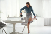 Young Woman Pouring Coffee Into Cup While Putting On Shoes At Home In Morning